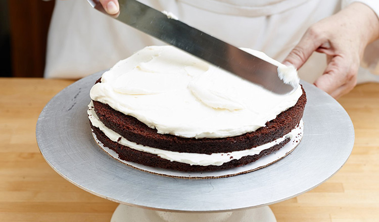 Spreading buttercream over layers of chocolate cake