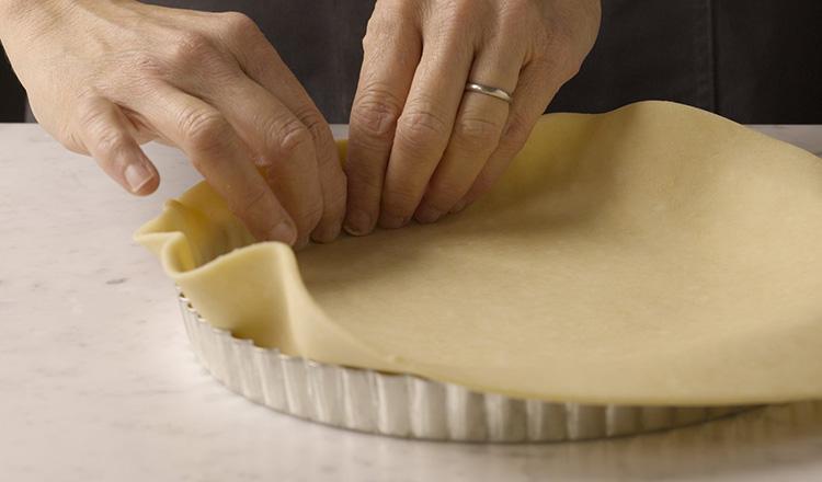 Vanilla tart dough being fitted into a tart pan