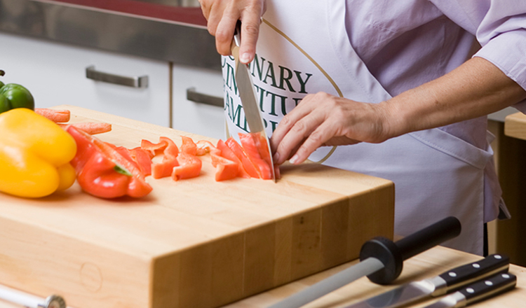 Chopping peppers with knives from The Culinary Institute of America tool kit.