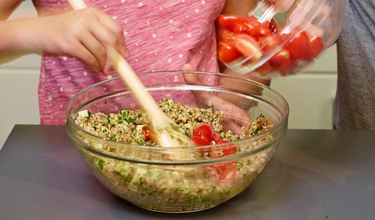 Mixing a farro caprese salad