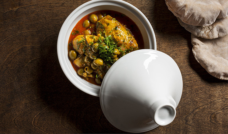Chicken thighs with green olives and pita served in a small white tagine.