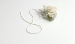 """The finished sachet d'épices, or """"bag of spices."""" Aromatic ingredients, encased in cheesecloth, that are used to flavor stocks and other liquids. A standard sachet contains parsley stems, cracked peppercorns, dried thyme, and a bay leaf."""