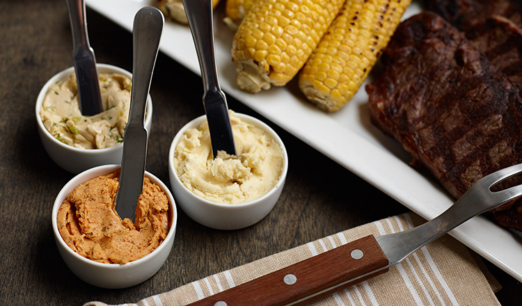 A trio of compound butters with grilled meats and vegetables.