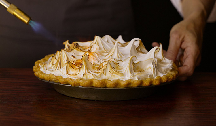 Use a culinary torch to evenly brown the exterior of a meringue topping.
