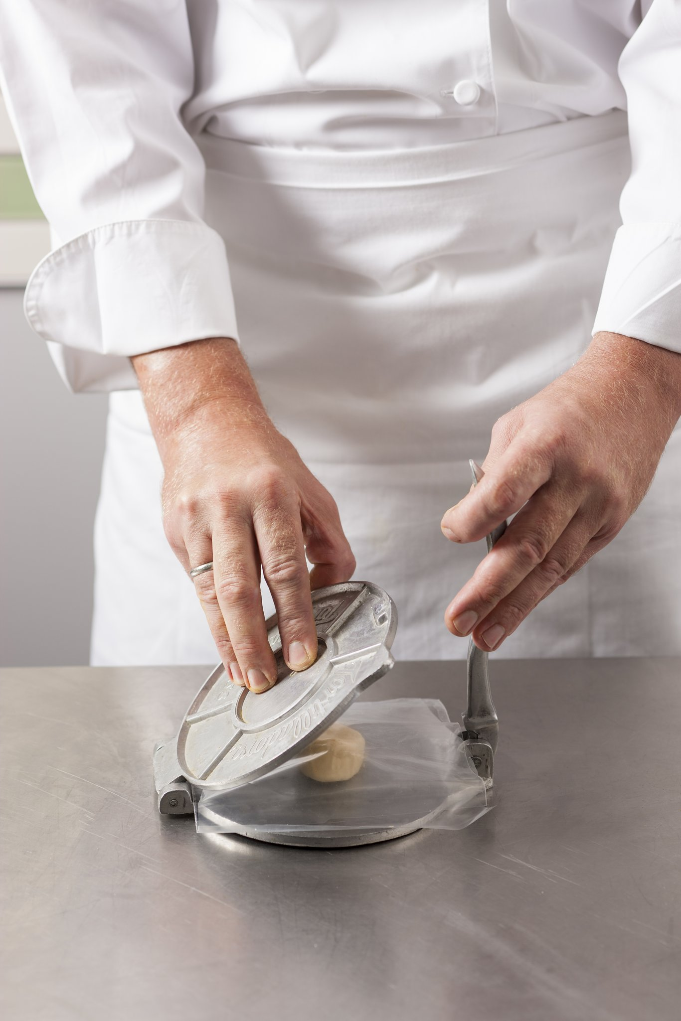 Pressing tortilla dough in a tortilla press.