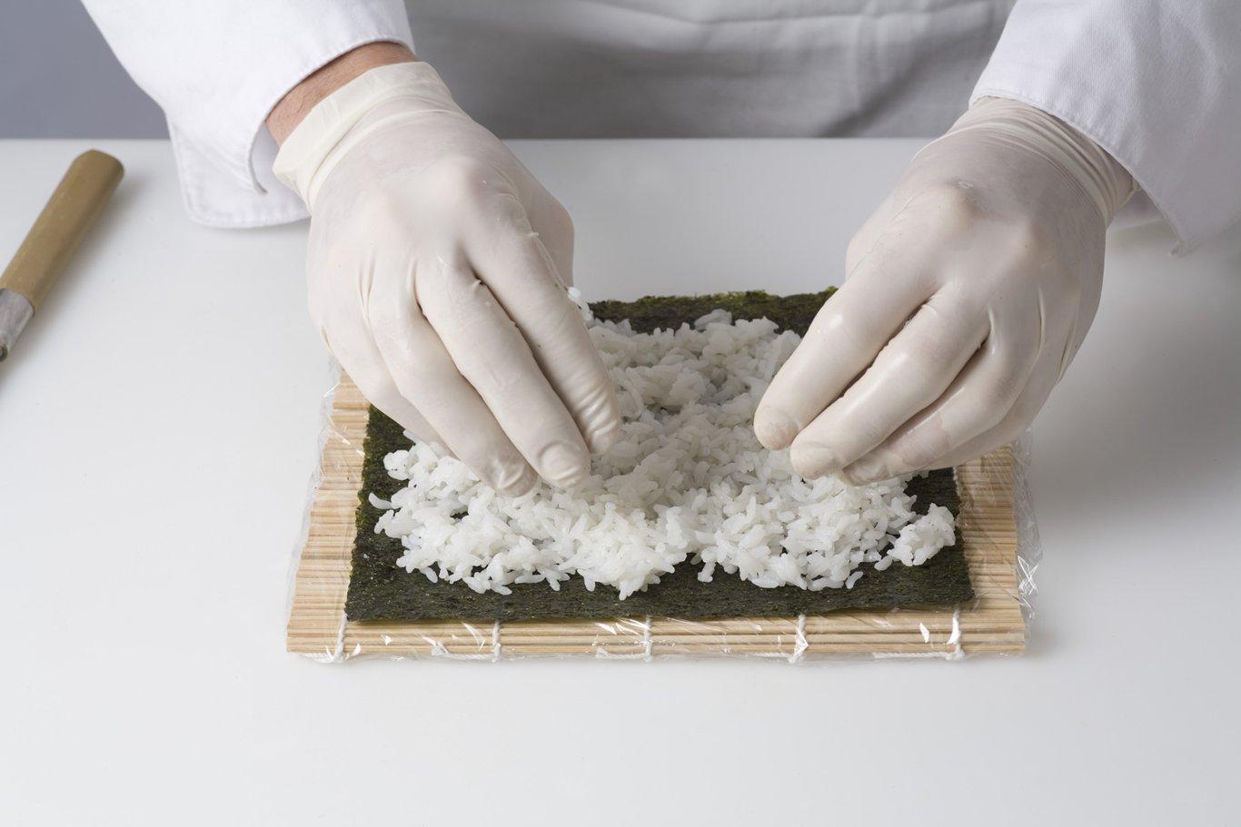 Spreading sushi rice on sheet or nori