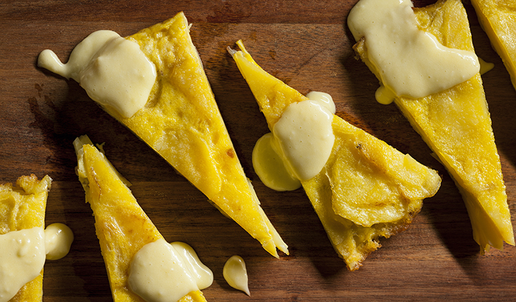 Spanish potato omelet topped with a white sauce