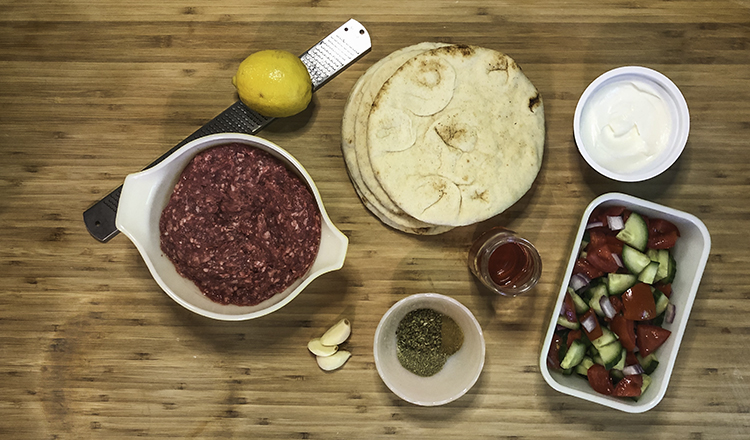 Ingredients for crispy lamb pitas, including lamb, yogurt, lemon, garlic, herbs, vegetables, and yogurt.