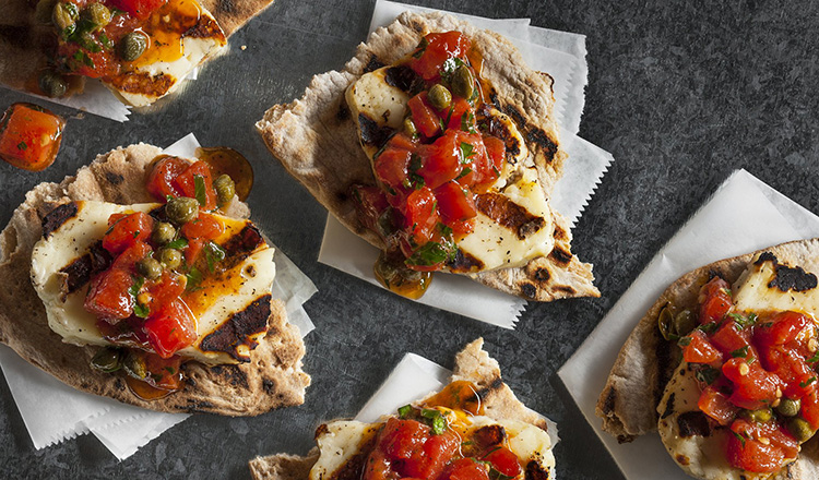Grilled east mediterranean cheese on a pita bread topped with tomatoes and capers