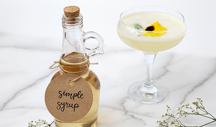 Simple syrup beside a cocktail.