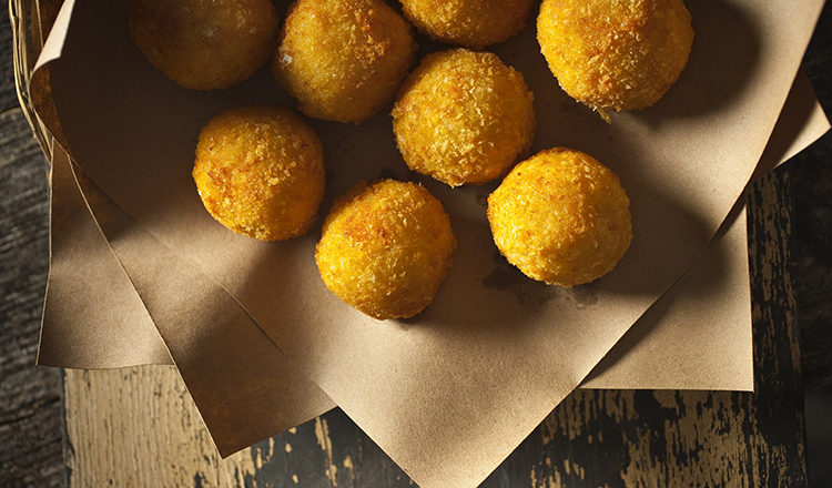 Breaded Risotto Fritters stuffed with Mozzarella and Sausage and served on brown paper