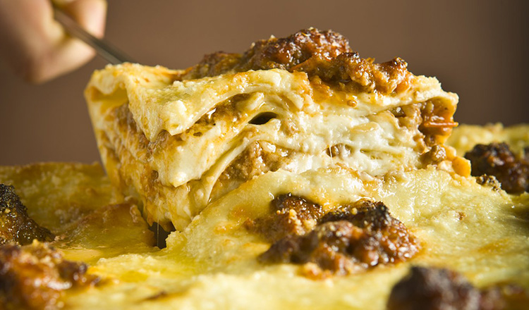 Traditional Lasagna alla Bolognese: layers of cooked pasta with bechamel and meat ragu.