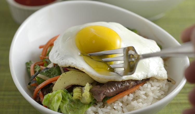 Bibimbap, mixed vegetables and meat over rice with hot sauce.