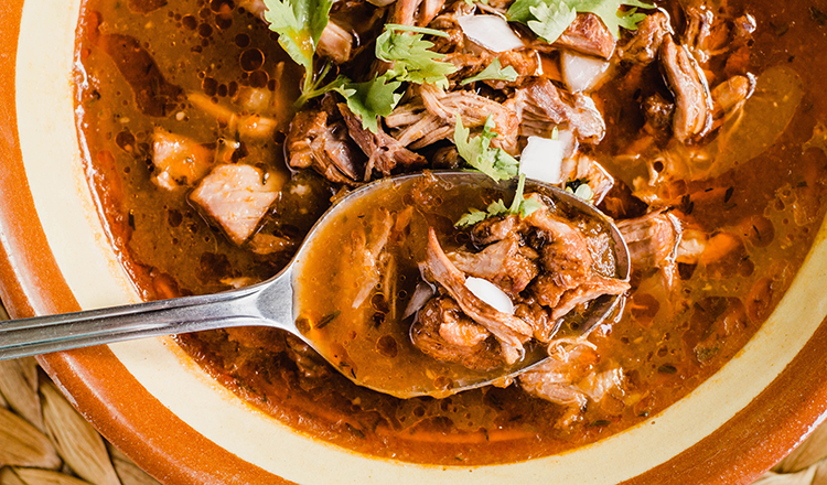 Traditional birria de res, a Jalisco style beef soup typical from Mexico. Close-up of the stew with a spoon
