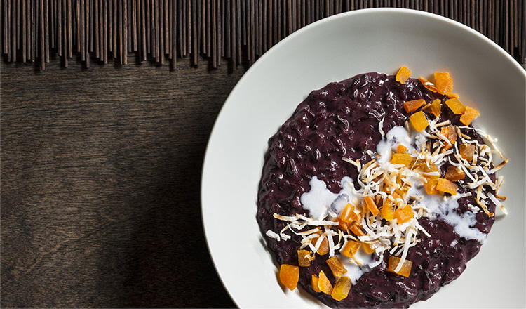 Purple rice pudding with dried mangos and toasted shredded coconut in a white round bowl.