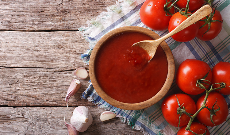 tomato ketchup with garlic and basil in a wooden bowl. horizontal view from above