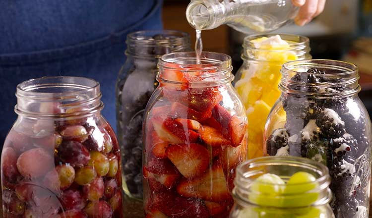 Pouring grappa into berry-filled jars