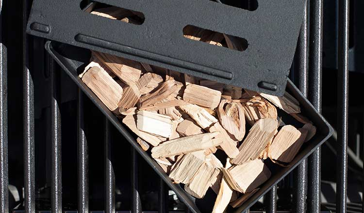 Wood chips in a smoker box, sitting on grill grates