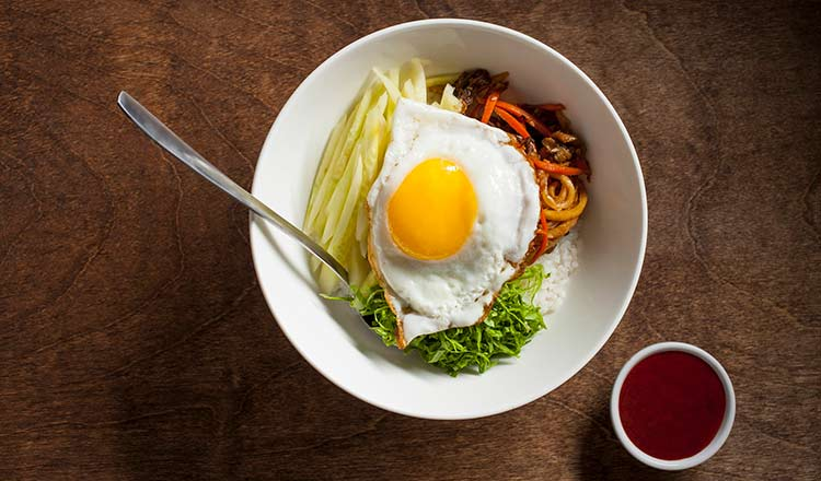 Fried egg over rice and vegetables